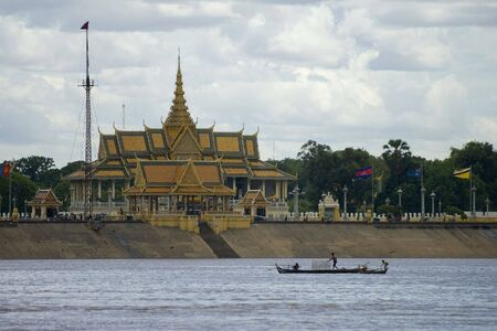 mekong: A fishing boat passes the palace on the banks of the Mekong, Cambodia
