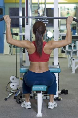 dorsi: A female fitness instructor demonstrates a lat pulldown