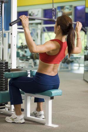 latissimus: Una donna che lavora ad una stazione di ritornare in una brughiera e centro fitness