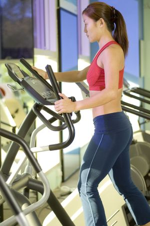 crosstrainer: A woman does some cardio exercise on a step machine