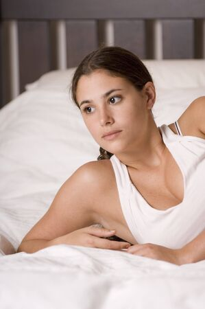 A pretty young woman lying on a bed stares into space photo