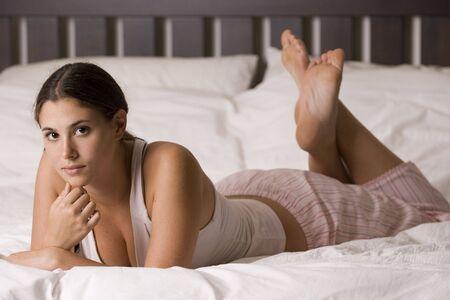 A naturally beautiful young woman lies on a kingsize bed in her pyjamas photo