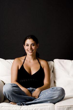 crosslegged: A beautiful young woman sits cross-legged on a white sofa Stock Photo