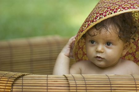 A toddler plays with a Vietnamese hat in a tropical garden photo