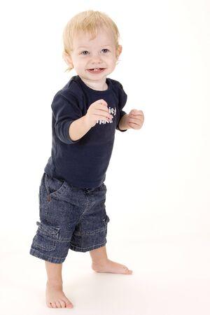 un niño rubio lindo está parado contra un fondo blanco Foto de archivo - 229795