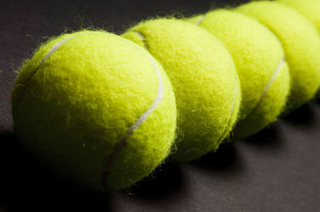 stillife: A macro shot of a line of tennis balls on a dark background. Shallow depth of field used.