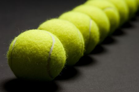 A macro shot of a line of tennis balls on a dark background. Shallow depth of field with focus on first ball. Stock Photo