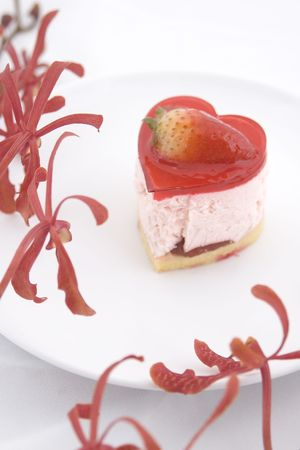 a heart-shaped strawberry cake on a white plate with orchids photo