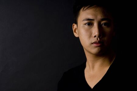 sidelight: A young chinese male models a black shirt on a black background Stock Photo