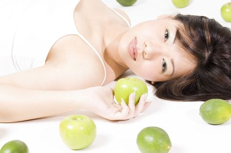 surrounded: A pretty young asian woman is surrounded by green fruits on a white background