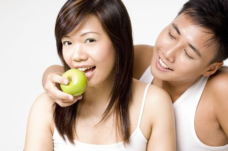An attractive male model feeds a pretty young asian woman an apple photo