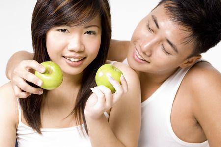 curare teneramente: Una coppia asiatica good-looking sana che mangia le mele. Bianco da portare su priorit� bassa bianca