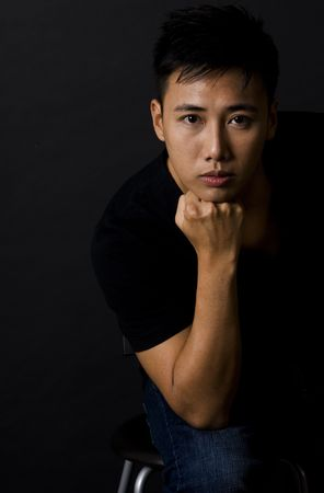 stares: A chinese male model sits on a stool and stares moodily at the camera Stock Photo