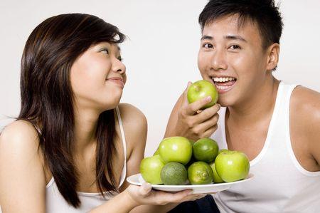 curare teneramente: Un maschio asiatico giovane mangia felicemente una mela verde offerta lui dal suo girlfriend grazioso
