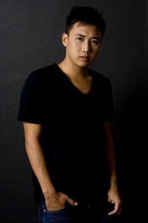 sidelight: A good-looking asian male model in black v-neck tee and jeans Stock Photo