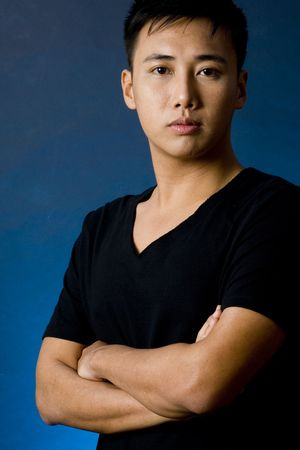 sidelight: A chinese male model in a black v-neck t-shirt on a blue backlit background Stock Photo