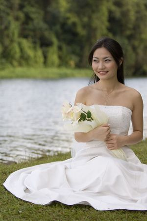 A beautiful asian woman in a wedding dress poses by the side of a lake, holding a yellow rose photo