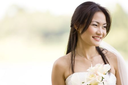 A beautiful asian bride poses outside photo