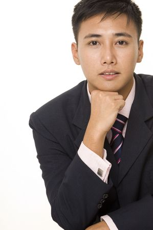 A young asian businessman in smart dress rests his chin on his fist photo