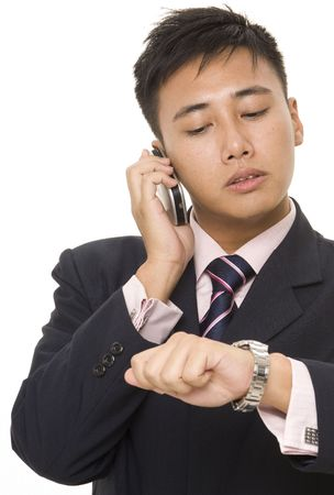 A young asian businessman looks at his watch whilst on the phone photo