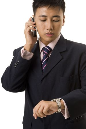 An asian businessman in navy and pink looks at his watch whilst on the phone photo