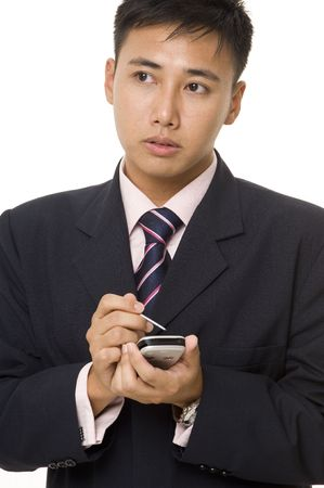 A young asian businessman ponders making notes on his handheld computer photo