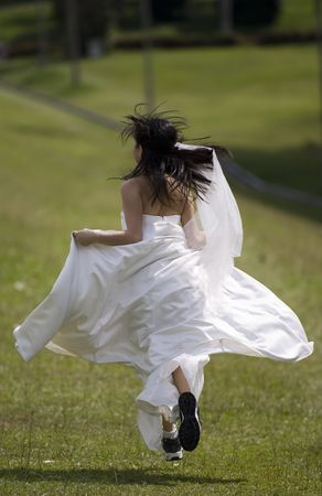 flee: A woman in her wedding dress runs away in training shoes
