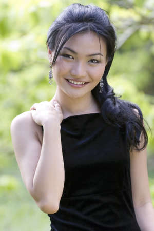demure: A beautiful and demure chinese woman in a black evening dress posing outside