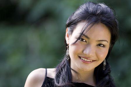poses de modelos: Un modelo chino hermoso se presenta afuera en un vestido de noche negro Foto de archivo