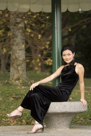 demure: A beautiful young asian woman poses on a concrete bench in a black evening dress