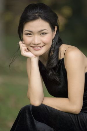 demure: A beautiful young chinese woman in a black dress posing outside