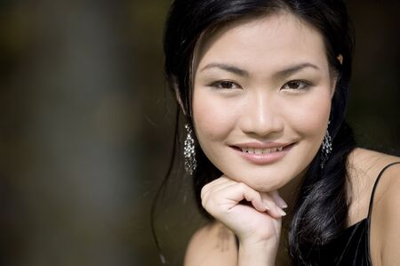 demure: A beautiful young asian woman poses outside