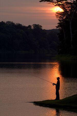 durchstechen: Ein Schattenbild eines Fischers als der Sonne stellt auf niedrigeres durchbohren Vorratsbeh�lter, Singapur ein
