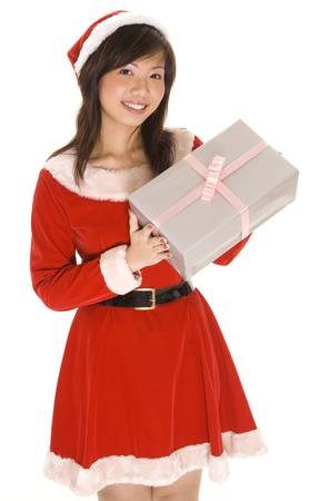 A cute asian girl in a santa costume has a big present wrapped in silver paper photo