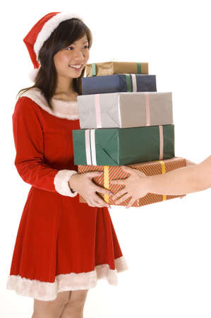 A cute female santa gives away a pile of presents photo
