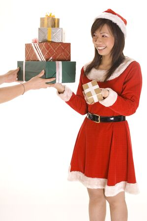 A cute asian woman in a santa costume holds a big pile of presents and one small one. Hands are reaching for the big pile photo