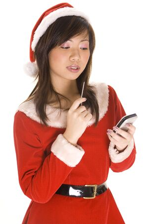 A cute asian girl dressed as santa checks her list on a personal handheld computer photo