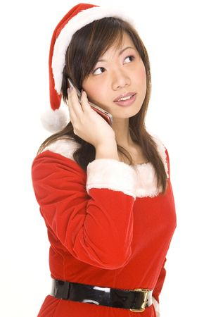 A cute asian woman dressed in a santa costime listens on the phone photo