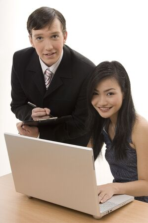 to assess: A businessman and woman work on a laptop computer - looking at the camera and smiling