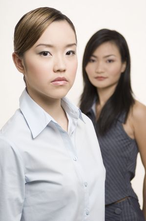 but: Two serious-looking but attractive asian businesswomen. One in focus, one deliberately out of focus. Stock Photo