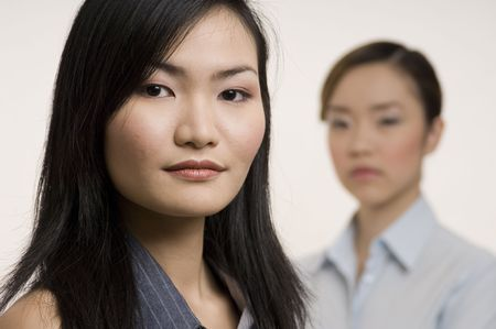 An attractive asian businesswoman with a colleague standing behind (out of focus) photo