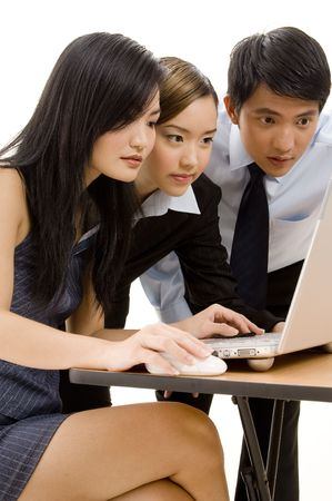 Three asian business people look at a laptop screen photo