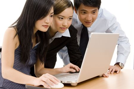 Three business people looking at a laptop computer Stock Photo - 247105