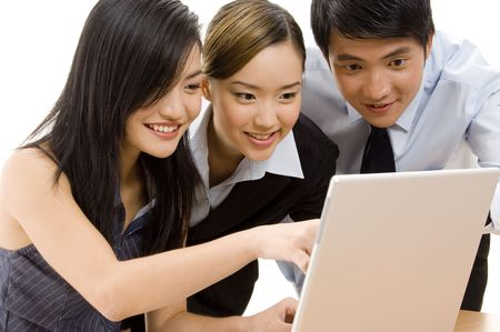 asian office lady: A group of three smiling business people working at a laptop computer