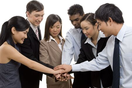 bonding: A group of six business men and women put their hands in for team bonding
