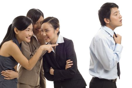 Three attractive young asian businesswomen gossip about one of their colleagues photo