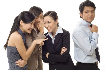 Three attractive young businesswomen gossip about a male co-worker photo