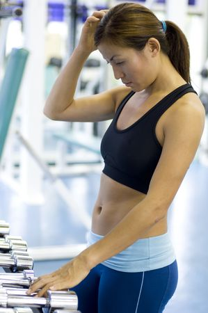 enthusiast: A female fitness enthusiast looks confused over which dumbbells to use