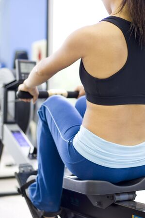 simulate: A female fitness instructor uses a rowing machine
