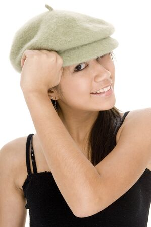 A funky young asian woman in a green hat on white background photo